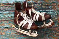 Vintage pair of mens  ice skates on a wooden wall Royalty Free Stock Photos
