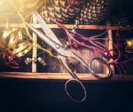 Vintage pair of scissors on wooden box with  Christmas decoration, retro toned Stock Photos