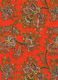 Vintage paisley fabric detail. Close-up of 60s-70s orange vintage fabric with black, white and yellow flowers and paisley designs, plus gold-colored threads Stock Photos
