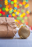 Vintage paper giftbox and gold colored christmas ball on blurred Royalty Free Stock Photography