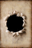Vintage Paper With Hole. Vintage paper with a hole torn in the middlewith black background stock image