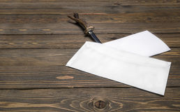 Vintage paper knife slits the envelope with a letter. Composition vintage paper knife slits the envelope with a letter lying on the table royalty free stock image