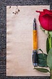 Vintage paper red scented rose fountain pen on wooden board Royalty Free Stock Photography