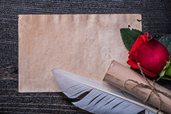 Vintage paper roll red rose feather on wooden Royalty Free Stock Photography