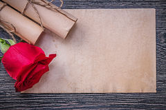 Vintage paper rolls red scented rose on wooden background Stock Images