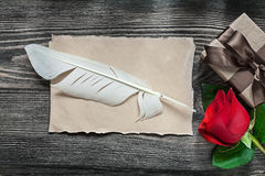 Vintage paper sheet feather red rose gift box on wooden board ho Stock Images