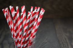 Vintage paper straws in glass on wood table Royalty Free Stock Images