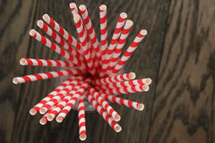 Vintage paper straws in glass on wood table Stock Images