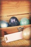 Vintage paper textures, Colorful easter egg in wood box with paper tag Stock Images