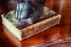 Vintage paper weight like a human fist on book. Black paper weight fist-shaped on antique book on wooden table Royalty Free Stock Photography