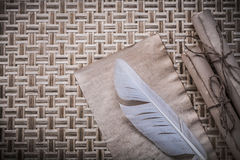 Vintage parchment paper rolls feather on wicker wooden surface Royalty Free Stock Images