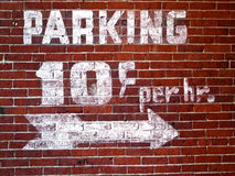 Vintage Parking Sign. Painted in white wash on a old brick building outside wall.  Sign reads Parking 10 cents per hour with a big white arrow pointing the way Stock Photo