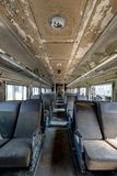 Vintage Passenger Car - Abandoned Train. Inside a vintage but abandoned passenger train car with brown cloth and vinyl seats Royalty Free Stock Photo