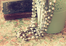 Vintage Pearl Necklace Over Floral Pattern Background. Retro Filter Royalty Free Stock Photography