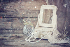 Vintage pearls , antique wooden jewelry box with mirror and perfume bottle on wooden table. filtered image Stock Photos
