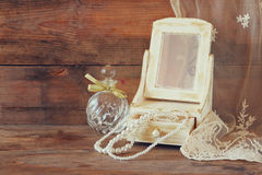 Vintage pearls , antique wooden jewelry box with mirror and perfume bottle on wooden table. filtered image Stock Photography