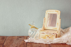 Vintage pearls , antique wooden jewelry box with mirror and perfume bottle on wooden table. filtered image Royalty Free Stock Image