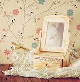 Vintage pearls , antique wooden jewelry box with mirror and perfume bottle on wooden table. filtered image Royalty Free Stock Photos