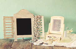Vintage pearls , antique wooden jewelry box with mirror and perfume bottle on wooden table. filtered image Stock Image