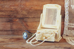 Vintage pearls , antique wooden jewelry box with mirror and perfume bottle on wooden table. filtered image Stock Photo