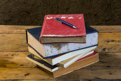 Vintage pencil and old books on wooden deck table with soil wall Royalty Free Stock Image