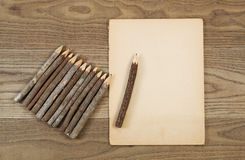 Vintage Pencils and Aged Paper on Rustic Wood. Overhead view of old pencils with tree bark and aged paper on rustic wood Stock Images