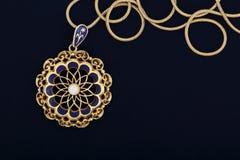 Vintage pendant. Macro of antique gold pendant on dark blue felt texture royalty free stock photo