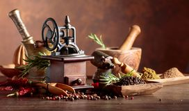 Vintage pepper mill with kitchen utensils, spices and rosemary on a old wooden table. Old pepper mill with kitchen utensils, spices and rosemary on a wooden royalty free stock photography