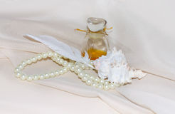 Vintage Perfume Bottle with feather, pearls and shellfish Stock Images
