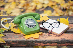 Vintage phone, book and glasses on bench in autumn park Stock Photography