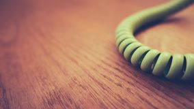 Vintage Phone Cord. Retro Vintage Phone Cord On Wooden Floorboards With Shallow Focus And Copy Space royalty free stock photography