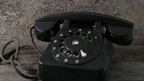 Vintage phone dolly in. Dolly in shot of old vintage rotary black phone. Tracking shot stock footage