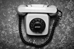 Vintage phone with a rotational dial on a concrete surface. Stock Image