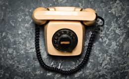 Vintage phone with a rotational dial on a concrete surface. Top view. Old technologies.  Royalty Free Stock Images