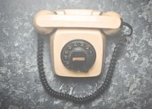 Vintage phone with a rotational dial on a concrete surface. Top view. Old technologies Stock Photography