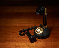 Vintage Phone on wooden desk. A black vintage phone on some wooden desk Stock Photography