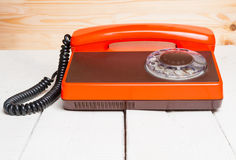 Vintage phone on wooden desk. Vintage phone closeup on wooden desk Stock Photography