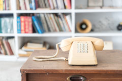 Vintage phone on wooden table, on bookshelf background Royalty Free Stock Photography