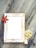 Beach album. Retro collection of the sea vacation - aged frame, photography blank, seashells and sea star on wooden background. Vintage page for your photo album Royalty Free Stock Photos