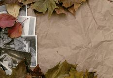 Nostalgia concept. Memoirs. Retro vintage background with copy space. Vintage photo album book laying in fallen autumn leaves and retro photos of peoples with Stock Photo