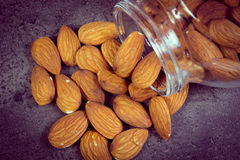 Vintage photo, Almonds spilling out of glass jar on concrete structure Stock Photography