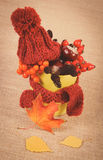 Vintage photo, Autumn decoration with cup wrapped scarf and woolen cap on burlap Stock Photo