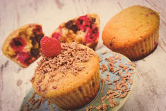 Vintage photo, Baked muffins with raspberries and grated chocolate on wooden background, delicious dessert Stock Image