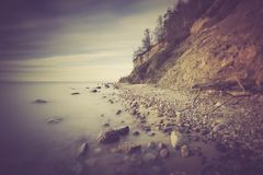 Vintage photo of Baltic sea shore with cliff in Gdynia Stock Images