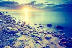 Vintage photo of beautiful rocky sea shore at sunrise Stock Photo