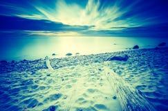 Vintage photo of beautiful rocky sea shore at sunrise Stock Image