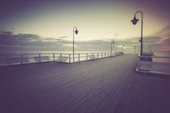Vintage photo of beautiful seascape with wooden pier. Royalty Free Stock Image