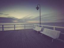 Vintage photo of beautiful seascape with wooden pier. Stock Images