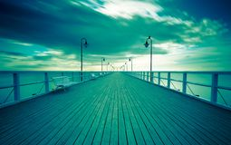 Vintage photo of beautiful seascape with wooden pier. Royalty Free Stock Images