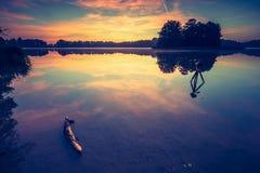 Vintage photo of beautiful sunrise over calm lake. Royalty Free Stock Image
